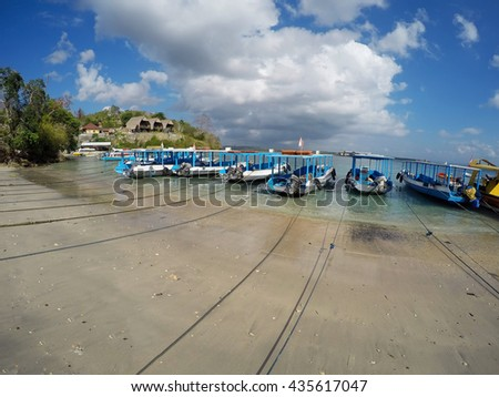 Catamarans grounded on sandy Nusa Penida beach, Bali Indonesia with blue sky. - stock photo