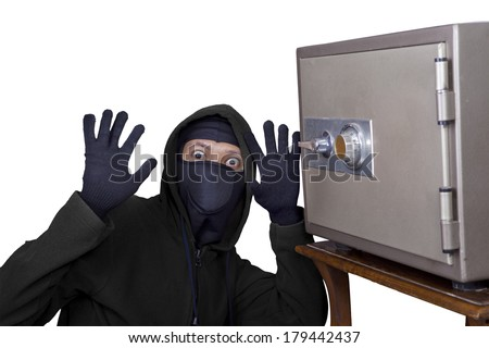 Catch the burglar concept, thief with balaclava caught in front a vault - stock photo