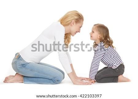 Catch this moment. Studio shot of an adorable mature woman sitting on her knees in front of her daughter nose to nose smiling on white background. - stock photo