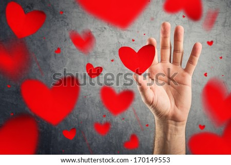 Catching hearts, Valentines day concept. Man holding red paper heart in his hand - stock photo