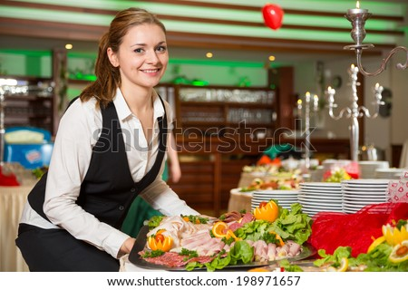 Catering service employee or waitress preparing a buffet - stock photo