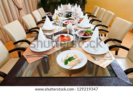 catering table set service with silverware and glass stemware at restaurant - stock photo