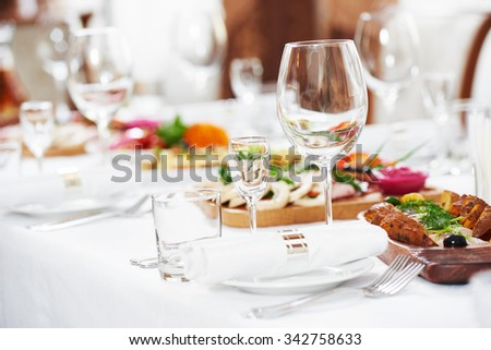 catering table set service with silverware, napkin and empty glass stemware at restaurant before party - stock photo