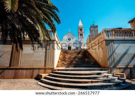 Cathedral in Supetar city with Palm and stairs on foreground on Brac island, Croatia - stock photo