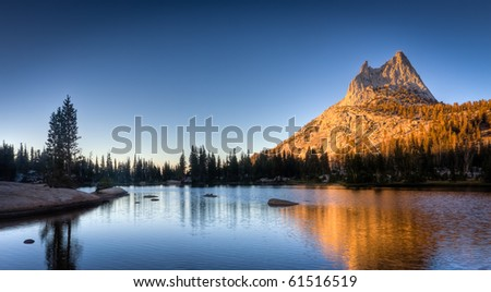 Cathedral Lake at Sunset. Cathedral Peak and pine trees are reflected in the beautiful blue water of Upper Cathedral Lake in Yosemite National Park - stock photo