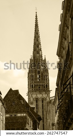 Cathedral of Quimper seen through the narrow street. Brittany, France. Aged photo. Sepia. - stock photo