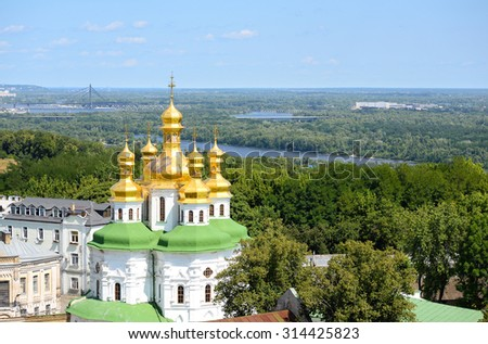 Cathedral of the Dormition, river Dniepr, blue sky and green trees background/Kyiv Pechersk Lavra/Cathedral of the Dormition and Refectory Church, Kyiv Pechersk Lavra, Kiev, Ukraine - stock photo