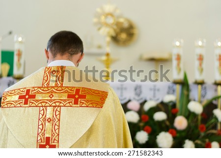 Catholic Church priest in yellow clothes bows to Crucifixion with flowers and candles - stock photo