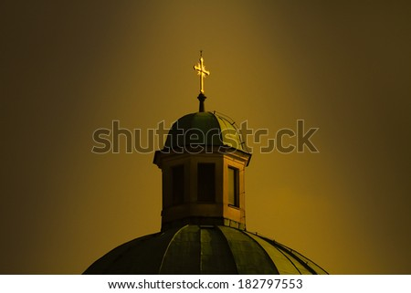 Catholic church with cross in golden glow - stock photo