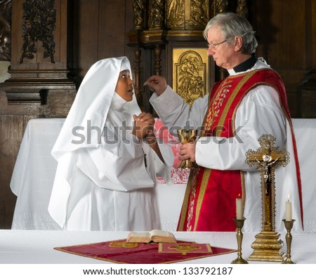 Catholic priest giving holy communion to a nun - stock photo