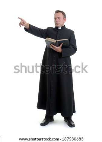 Catholic priest preaching while holding a Bible, against a white background. - stock photo