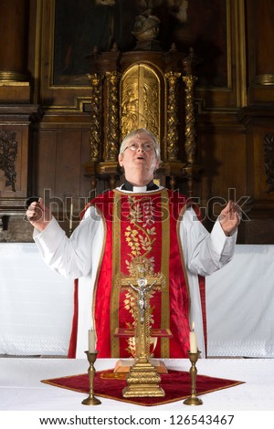 Catholic priest saying a prayer during mass in a medieval church with 17th century interior (including the painting) - stock photo