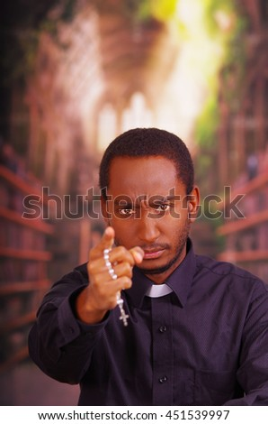 Catholic priest wearing traditional clerical collar shirt standing facing camera, holding hands out with rosary cross, looking forward, religion concept - stock photo
