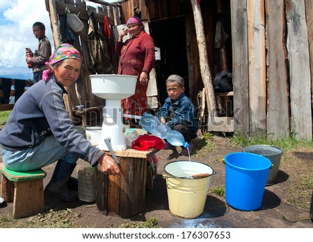 Cattle camp in the mountains of Mongolian Altai. Processing of milk - stock photo