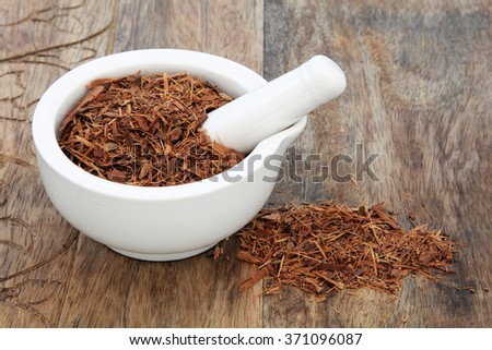 Catuaba bark herb used in natural alternative herbal medicine in a mortar with pestle over old wood background. Used as an aphrodisiac to increase libido. - stock photo