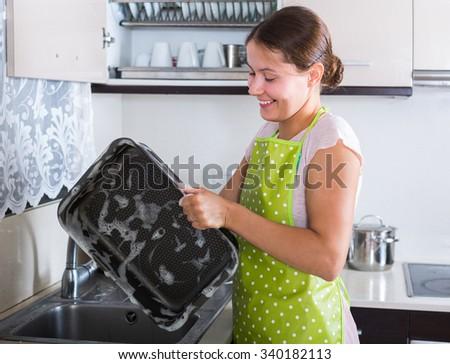 caucasian adult brunette washing kitchenware indoors - stock photo