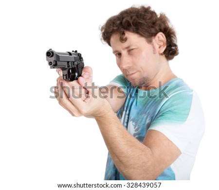 Caucasian adult man aiming with black gun in hands, isolated on white background, focus on weapon - stock photo