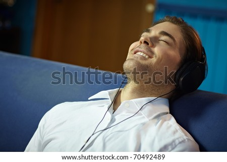 caucasian adult man relaxing on sofa with headphones. Horizontal shape, side view, head and shoulders, copy space - stock photo