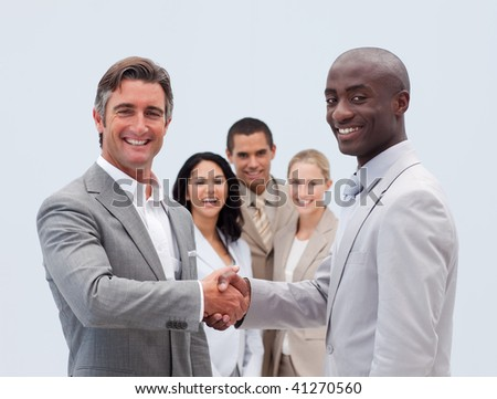 Caucasian and Afro-American businessmen shaking hands with his colleagues in the background - stock photo