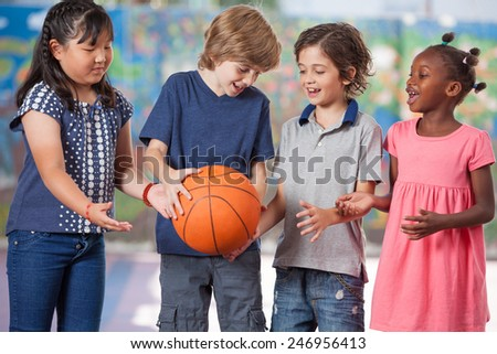 Caucasian, asian and afroamerican primary students playing basketball. - stock photo