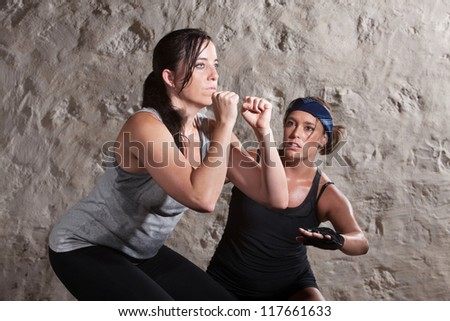 Caucasian athlete sweating with trainer in boot camp training workout - stock photo