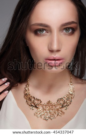 Caucasian attractive sexy fashion model with long brunette natural hair, beautiful eyes, full lips, perfect skin. Decoration of around his neck. - stock photo