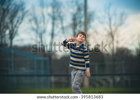 Caucasian autistic boy in striped shirt pretends to throw a ball outside - stock photo