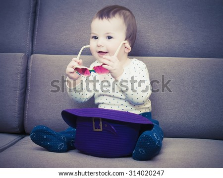 Caucasian baby boy hold glasses sitting on brown sofa at home - stock photo