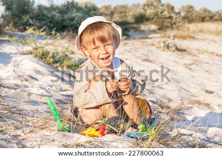 Caucasian baby (boy) is sitting at the beach with sand dunes. Cute child is playing with toys and having fun in summer day. Close up, outdoor.   - stock photo