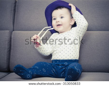 Caucasian baby boy with a hat sitting on brown sofa at home - stock photo