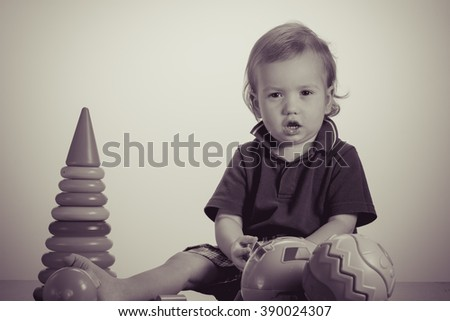 Caucasian baby playing with a toy pyramid. Photo in vintage style of old pictures - stock photo