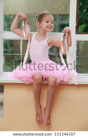 Caucasian ballerina warming up in pointes in the ballet hall on the wooden dance floor - stock photo