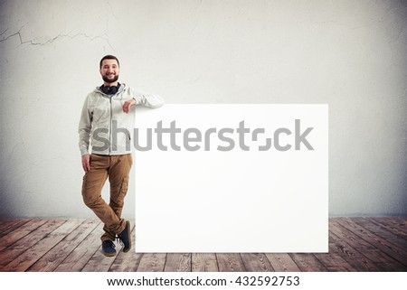 Caucasian bearded man in casual clothes is standing with his elbow resting on a big white poster in white room with wooden floor - stock photo