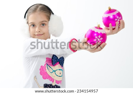 Caucasian beautiful little girl  holding a  Christmas decorative pink balls for Christmas tree decoration/Smiley girl holding pink decorative balls  - stock photo