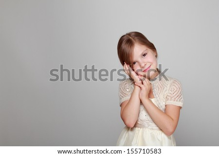 Caucasian beautiful little girl in dress with long hair on grey background - stock photo