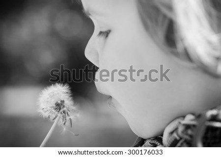 Caucasian blond baby girl and dandelion flower in a park, monochrome photo with selective focus - stock photo