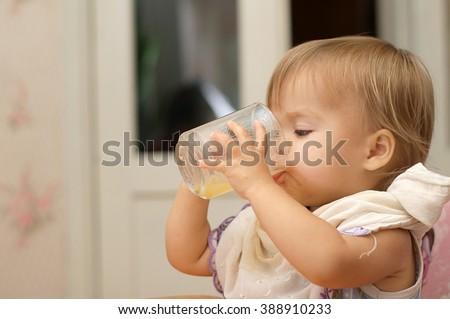 Caucasian blonde little girl drinking natural juice  - stock photo