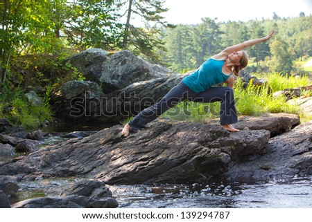 caucasian blonde middle-aged woman practicing yoga in side angle pose ion rocks beside stream, Surry, Maine, Summer - stock photo