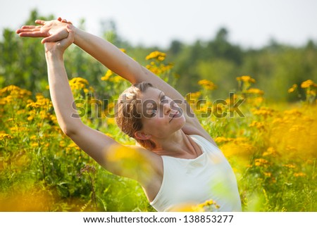 Caucasian blonde woman stretching in yoga pose in the middle of a meadow of ragweed flowers.  Blue Hill, Maine, Summer - stock photo