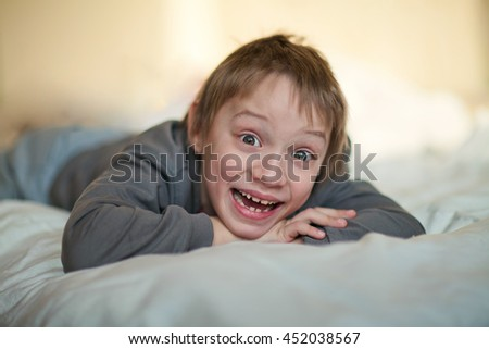 Caucasian boy, age 7 years, expresses different emotions, happy, laughing, lying on the bed in the apartment - stock photo