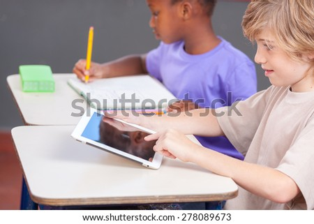 Caucasian boy and afro american girl at school with tablet and book. - stock photo