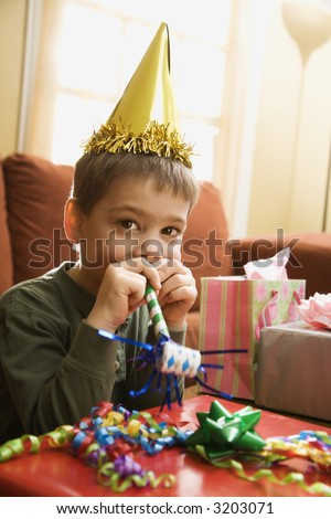 Caucasian boy at  birthday party looking at viewer blowing noisemaker. - stock photo