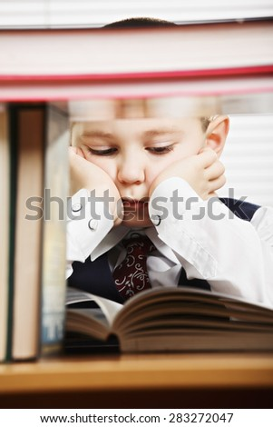 Caucasian boy behind books reading while leaning on palms - stock photo