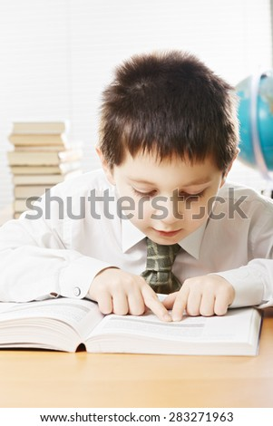 Caucasian boy reading by syllables while sitting at the desk in classroom - stock photo