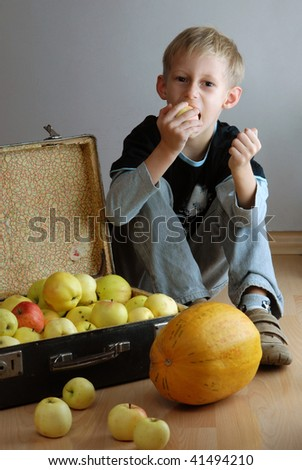 Caucasian boy sitting on floor near vintage suitcase filled with apples - stock photo