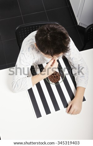 Caucasian brunette boy eating cereal from the bowl while sitting at kitchen table closeup above view - stock photo