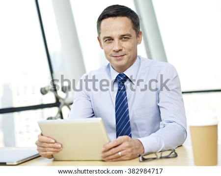 caucasian business executive sitting at desk looking at camera holding tablet computer in office. - stock photo
