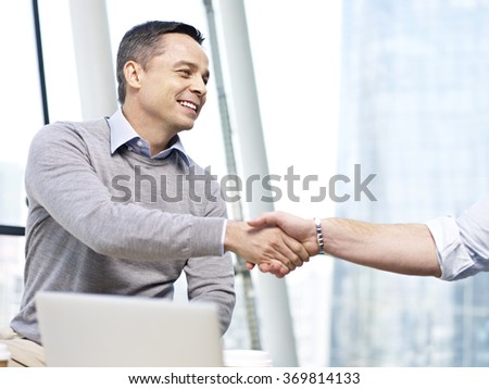 caucasian business executive smiling and shaking hand with another person in office. - stock photo
