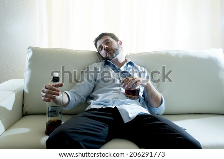 caucasian businessman alcoholic wearing a blue work shirt and tie drunk and drinking  Scotch or Whisky sitting on a sofa at home after a long day or week of work on a white background.  - stock photo