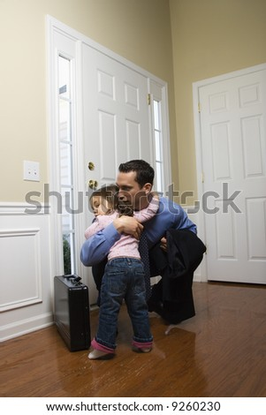 Caucasian businessman   at door with briefcase hugging daughter. - stock photo